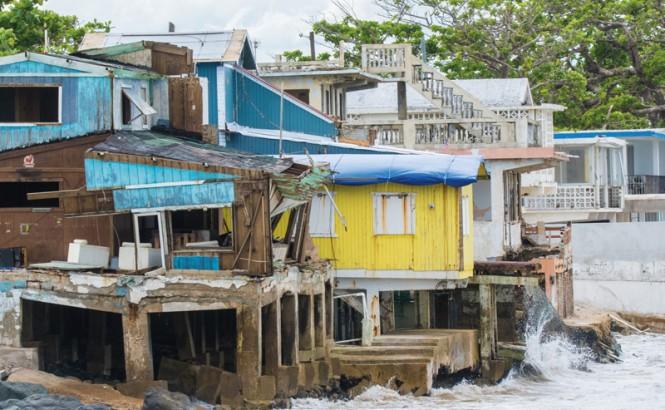 La fotografía muestra pequeños edificios de color turquesa, amarillo y blanco situados directamente sobre el agua en una costa en Rincón, Puerto Rico. Las aguas turbulentas son visibles. Rincón sufrió daños graves en el huracán María. Crédito: cestes001 (iStock / Getty Images Plus)