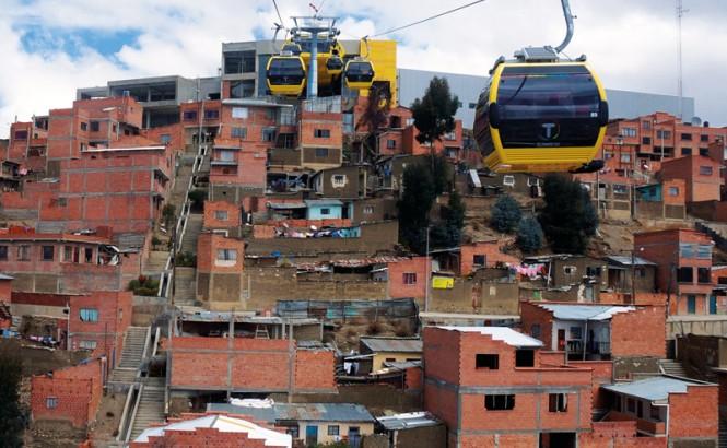 Teleféricos aéreos amarillos viajan por una colina en América Latina sobre asentamientos informales hechos de ladrillos. Crédito: Gwen Kash