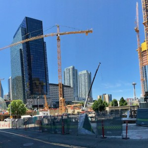 Two skyscrapers stands in front of a background of blue sky, with a crane in between.